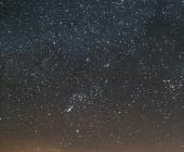Orion s Býkem, Plejádami a Jupiterem nad svítícími městy schovanými pod mraky.